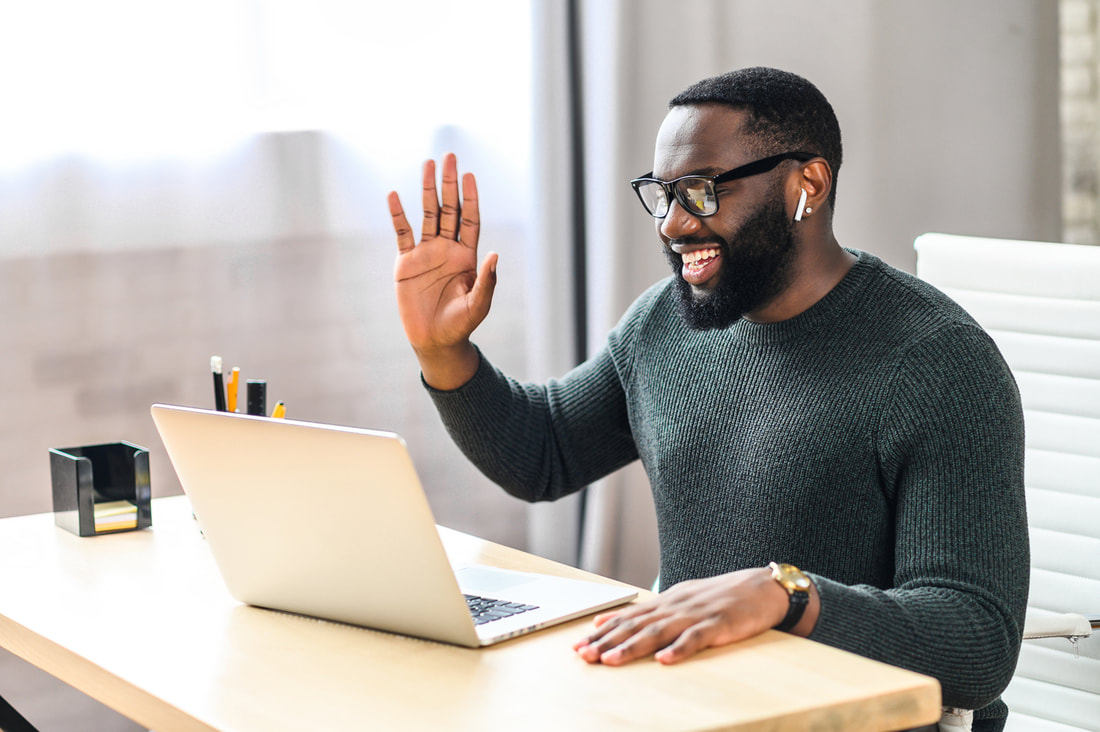 man smiling and waving to friends online
